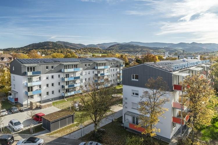 Wohnblöcke mit Balkons, im Hintergrund Berge