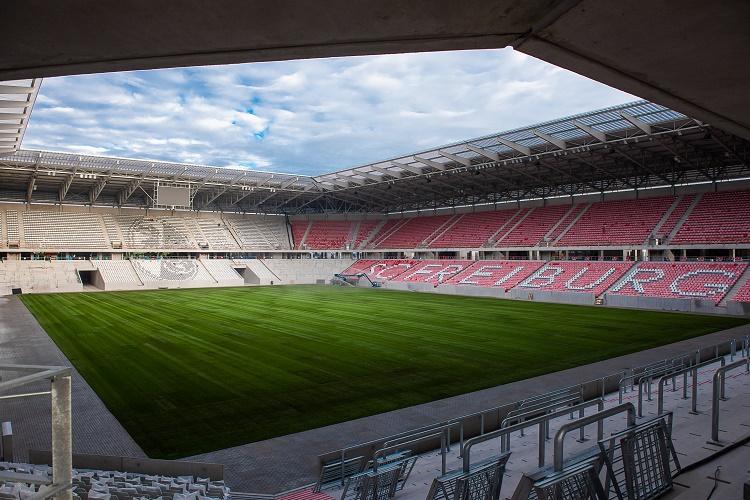 Blick ins Stadion mit Rasenfläche und Sitz- und Stehplätzen